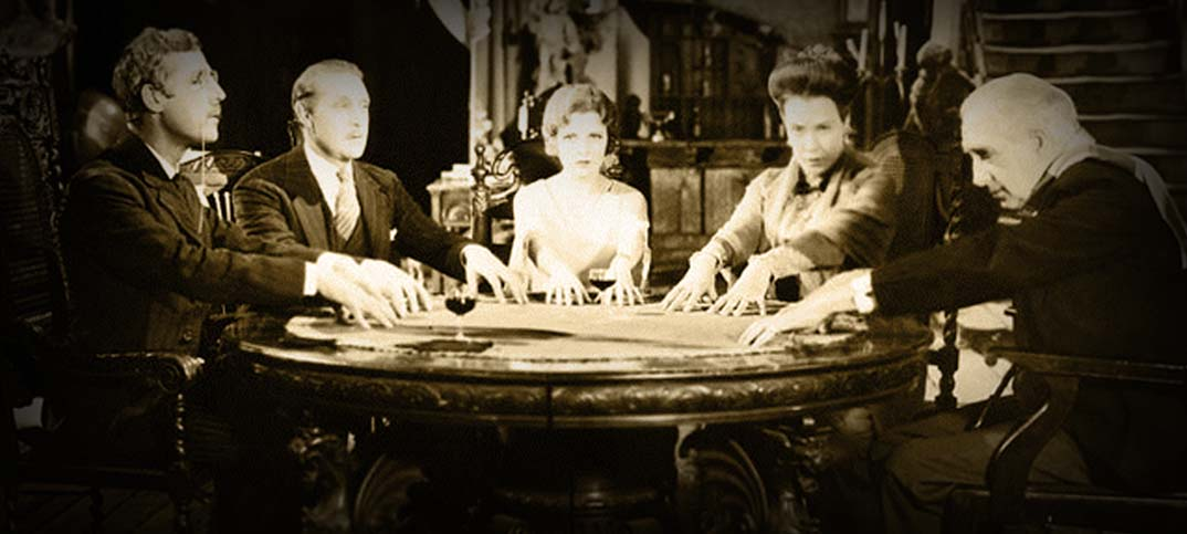 Photo from old movie of people holding a séance