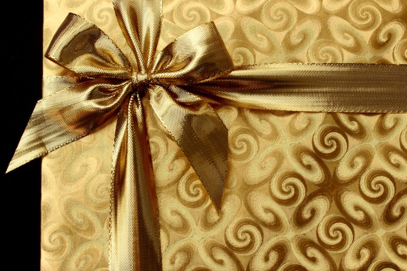 gift wrapped in gold paper with gold bow